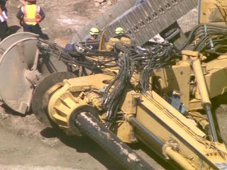 Drilling rig falls near airport, worker trapped